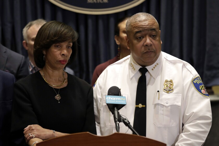 """IN this Feb. 11, 2019 photo, Baltimore Mayor Catherine Pugh, left, and Michael Harrison, center, acting commissioner of the Baltimore Police Department, listen to a reporter's question at an introductory news conference for Harrison in Baltimore. Police say a 2-year-old boy was wounded by gunfire when someone shot into a vehicle in an act of road rage, Saturday, Oct. 12. Harrison says the boy is in """"somewhat stable condition"""" and is expected to survive. (AP Photo/Patrick Semansky, File)"""