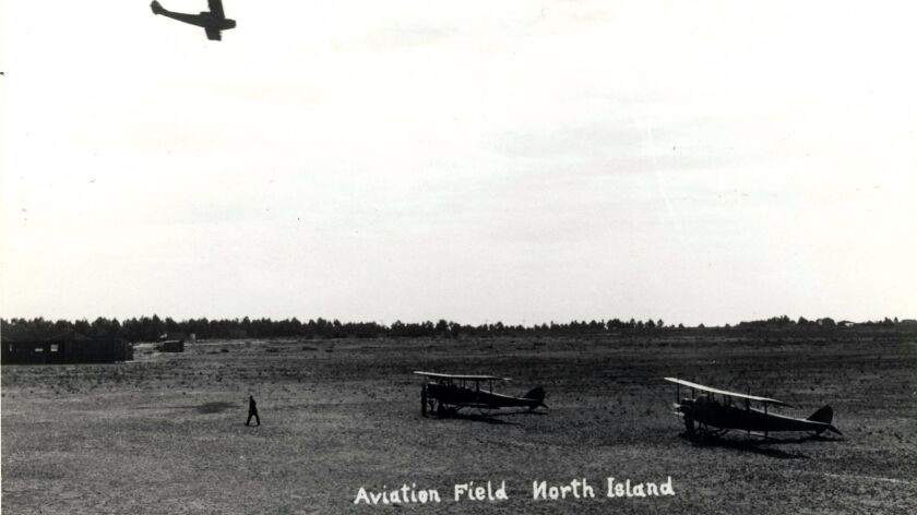 Curtiss JN landing at the aviation grounds on North Island while two other Curtiss planes wait on gr