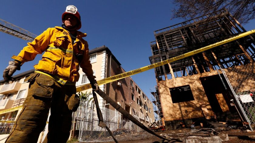 L.A. City Fire captain Tim Gill pulls hoses at the scene in the 400 block of Helitrope Drive in East