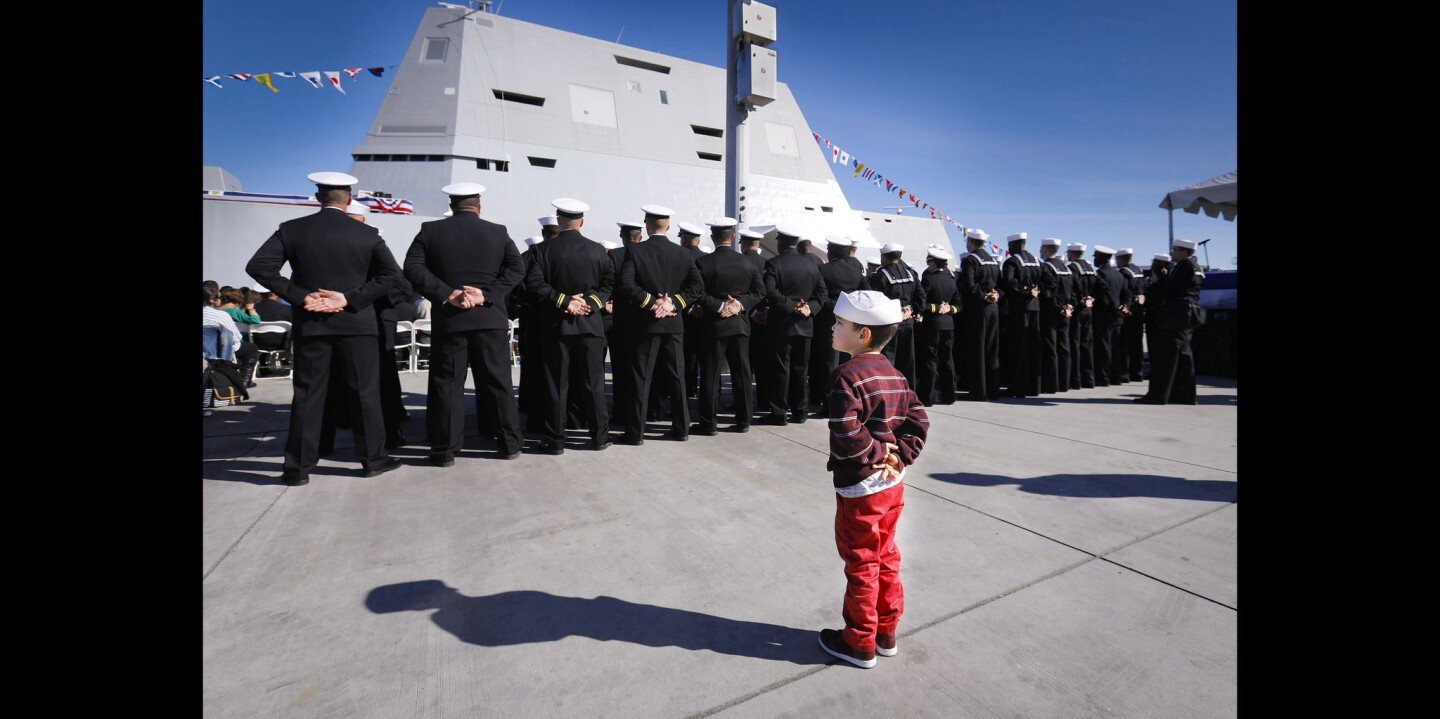 Four-year-old Nicolas Gazza, wearing a traditional Navy dixie cup cover, stands behind members of the USS Michael Monsoor crew during the commissioning ceremony at Naval Air Station North Island for the Navy's newest Zumwalt-class destroyer, named for Michael Monsoor, a Navy SEAL who was killed in action on September 29, 2006, in Ramadi, Iraq. Nicolas' mom, Rebecca Church, is a crew member on the ship.