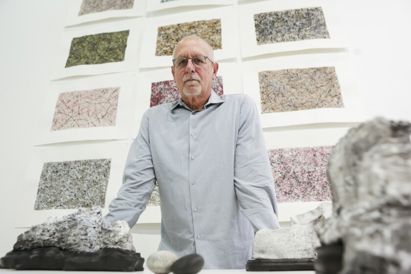 "Artist and curator Richard Turner stands in front of his drawings of ""Viewing Stones"" at Chapman University's Guggenheim Gallery. The show features large stones shaped by erosion, as well as many artworks that were inspired by the various rocks and objects on display."