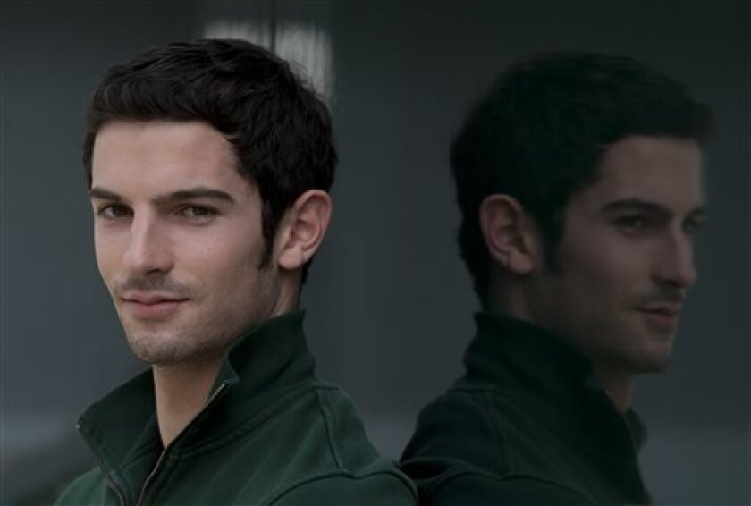 In this June 29, 2013 photo, American Caterham driver Alexander Rossi poses at the Silverstone circuit in Silverstone, England. As Formula One expands its reach into the United States, there remains one missing ingredient that could keep some fans away from the grand stands _ an American driver on the grid.(AP Photo/Jon Super)