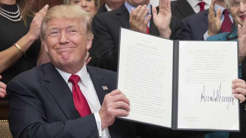 President Trump holds up an executive order on healthcare after signing it during a ceremony in the Roosevelt Room in October 2017.