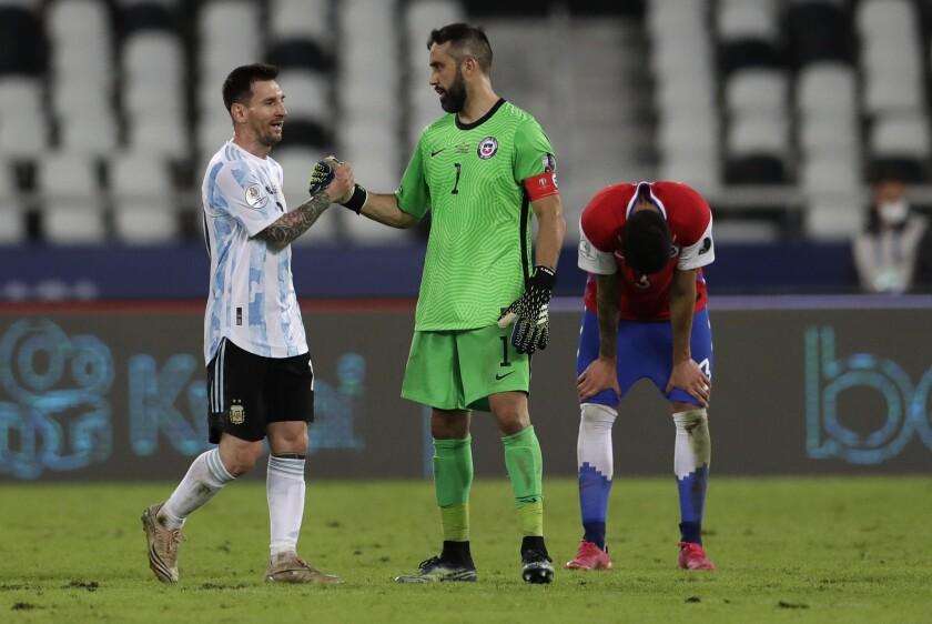 Lionel Messi, de Argentina, estrecha la mano del arquero Claudio Bravo, de Chile, tras el empate en el estadio Nilton Santos de Río de Janeiro, el lunes 14 de junio de 2021, en la Copa América (AP Foto/Ricardo Mazalan)