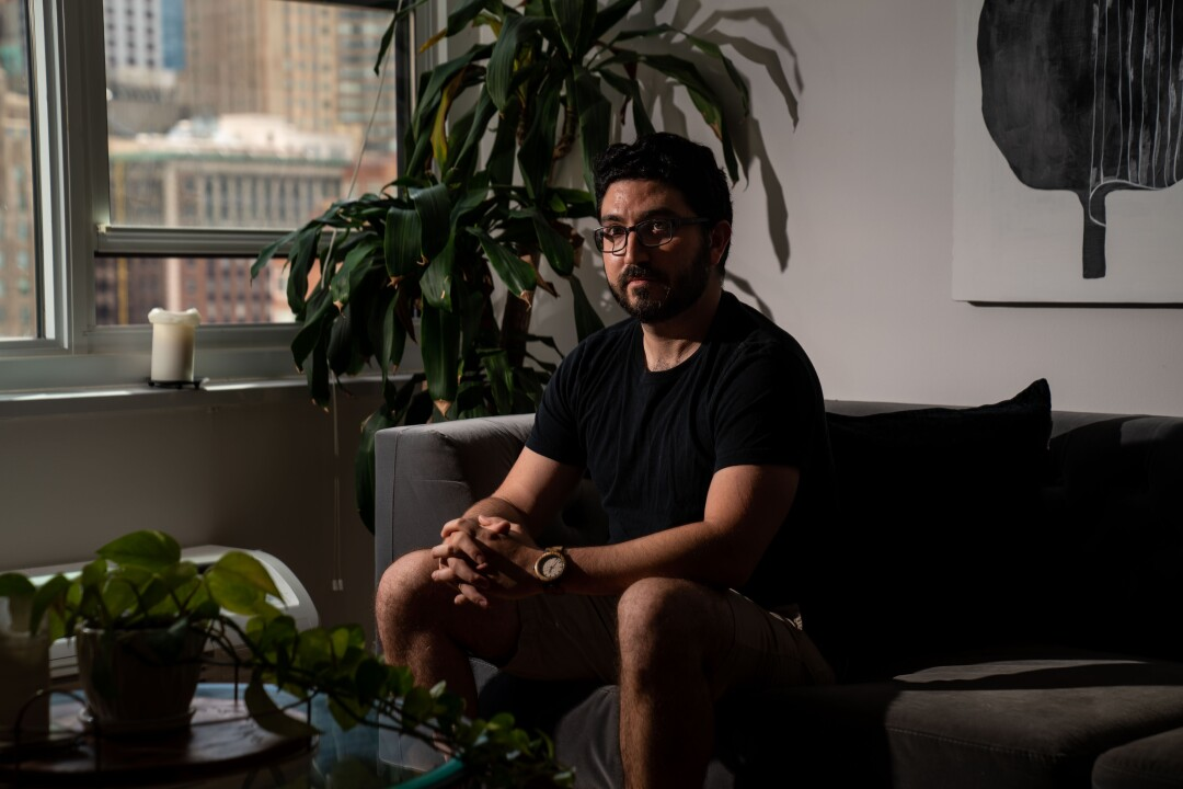 A man sits in his residence next to a plant and a window.