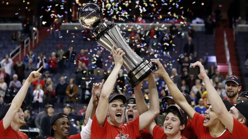 Davidson forward Peyton Aldridge, center, holds the trophy with his teammates after winning the Atlantic 10 conference tournament last March.