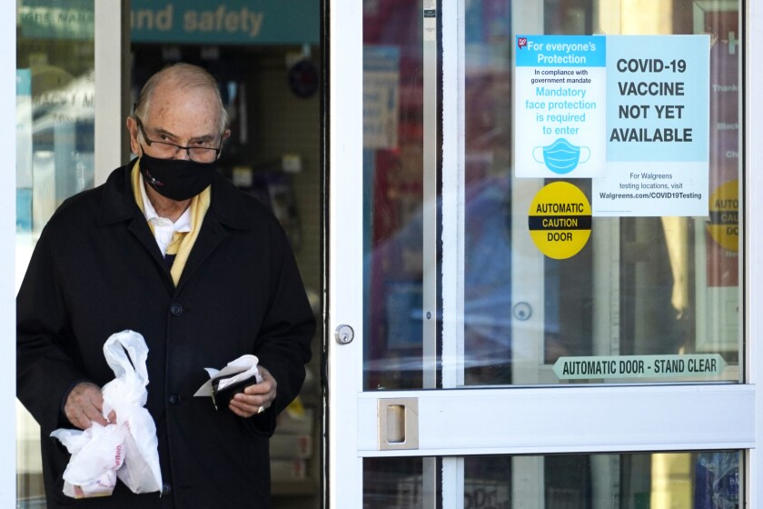A customer wears a mask as he walks out of a Walgreen's pharmacy store and past a sign advising that a COVID-19 vaccine is not yet available at Walgreens in Northbrook, Ill., Thursday, Dec. 4, 2020. (AP Photo/Nam Y. Huh)