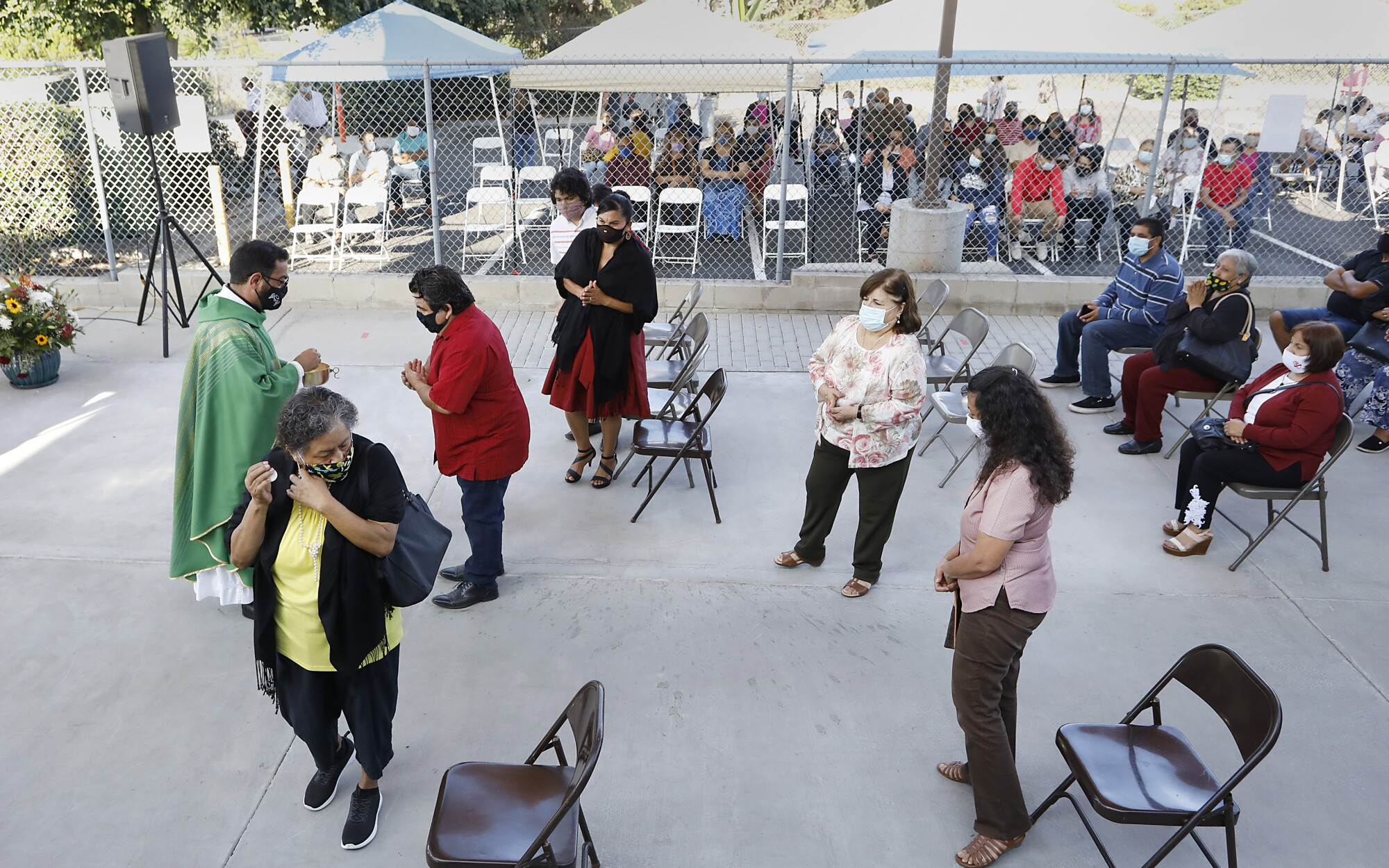 The Rev. Edmundo Zárate distributes communion at San Diego's St. Jude Shrine of the West.