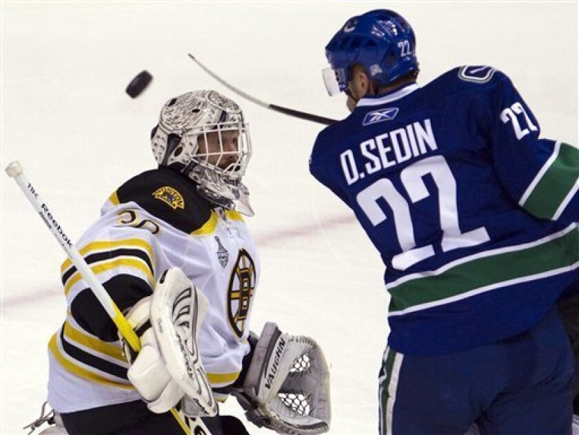 Vancouver Canucks left wing Daniel Sedin tries to bat down a loose puck in front of Boston Bruins goalie Tim Thomas during the first period of Game 5 of the Stanley Cup hockey finals in Vancouver, British Columbia on Friday, June 10, 2011. (AP Photo/The Canadian Press, Jonathan Hayward)
