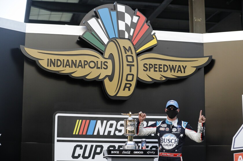 Race driver Kevin Harvick celebrates after winning the NASCAR Cup Series auto race at Indianapolis Motor Speedway.