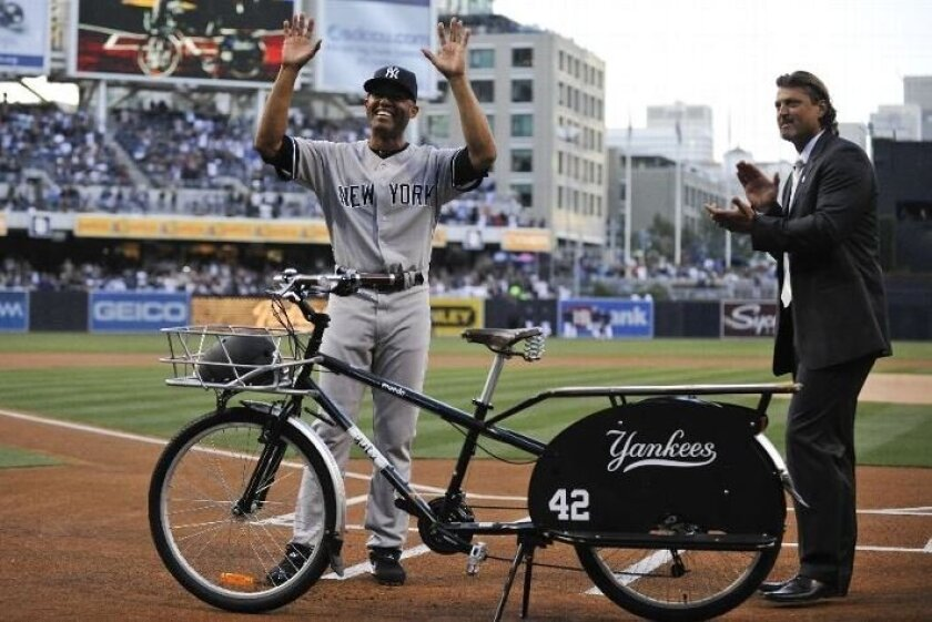 Former San Diego Padres pitcher Trevor Hoffman (R) claps as Mariano Rivera #42 of the New York Yankees is presented with a beach cruiser bike before a baseball game between the New York Yankees and the San Diego Padres at Petco Park on August 2, 2013 in San Diego, California. (Denis Poroy/Getty Ima