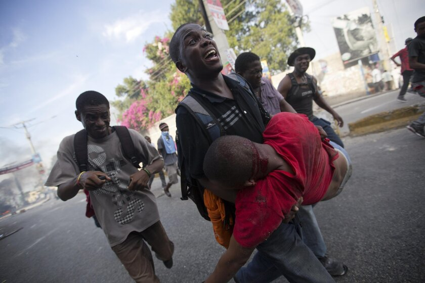 An opposition protester carries a fellow demonstrator injured by a machete when he was attacked by a resident in a neighborhood known for it's support of the ruling party, during a protest march against official preliminary election results, in Port-au-Prince, Haiti, Friday, Nov. 20, 2015. Residents began throwing rocks at marchers as they made their way through the neighborhood. One protester was killed by a gunshot, when police intervened in the clashes between the residents and protesters. The presidential runoff election is Dec. 27. (AP Photo/Dieu Nalio Chery)