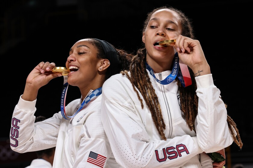 United States forward A'Ja Wilson and Brittney Griner bite their gold medals.