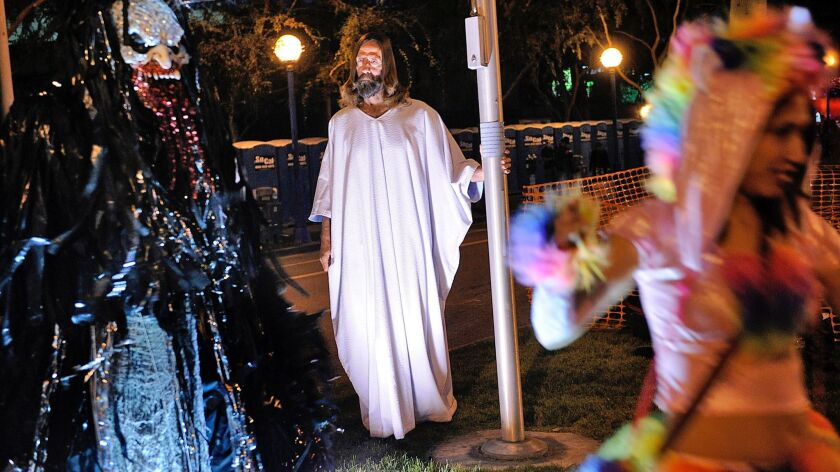 Kevin Short, dressed as Jesus, looks on as people take photos during the Halloween Carnaval in West Hollywood in 2013.