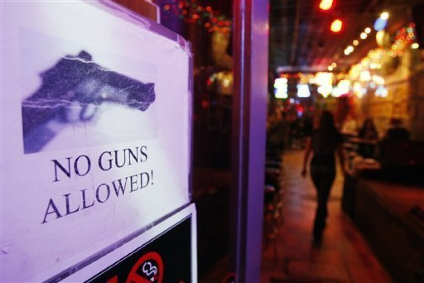 A sign declaring that no guns are permitted is posted on the door of Tootsie's Orchid Lounge in on Thursday, Dec. 10, 2009 in Nashville, Tenn. In Tennessee, properly licensed handgun owners won the right to carry their weapons into bars, restaurants that serve alcohol, sports fields and even playgrounds, but many bars have since decided to keep gun bans in place and more than 70 communities have opted out of allowing guns in parks. (AP Photo/Mark Humphrey)
