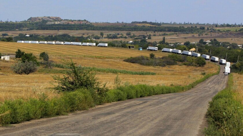 The first trucks of a convoy purportedly carrying Russian aid head to Luhansk after crossing the border into eastern Ukraine on Aug. 22.