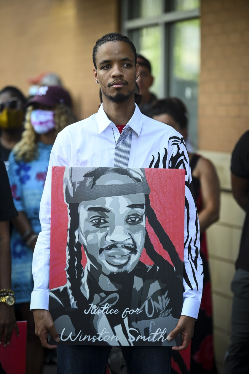"""FILE - In this June 10, 2021 file photo, Kidale Smith, brother of Winston Smith, holds a """"Justice for Winston Smith"""" poster during a press conference in Minneapolis. A Minnesota prosecutor is reviewing evidence in the U.S. Marshal Services' fatal shooting of Winston Smith Jr. during an arrest. Crow Wing County Attorney Donald Ryan said he'll review the evidence on his own and hopes to have a charging decision by mid-October. (Aaron Lavinsky/Star Tribune via AP File)"""