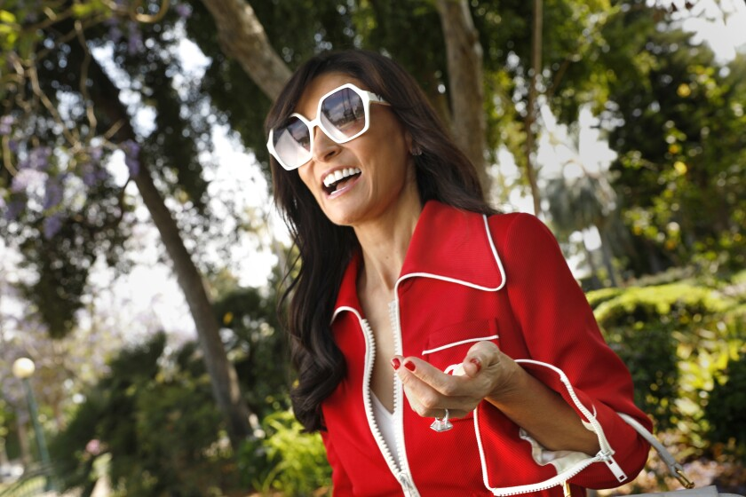 Julia Haart stands in a park wearing a red jacket and white sunglasses.