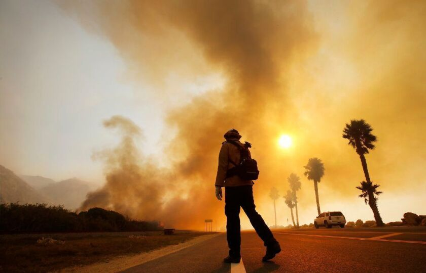 A firefighter monitors the Thomas fire burning alongside the 101 Freeway on Dec. 7, 2017.