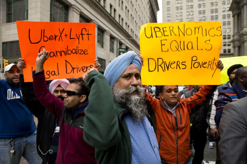 Ubernomics: Who benefits? Taxi and Uber drivers protest the ride-hailing services Uber X and Lyft last month in Philadelphia.