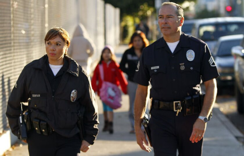 LAPD officer Wendy Reyes and Sargeant Frank Preciado patrol the sidewalk at Main Street Elementary in Los Angeles in January, after the attack on a school in Connecticut. The LAUSD has hired more than 750 of the 1,000 security aides it decided to hire after the December shooting.