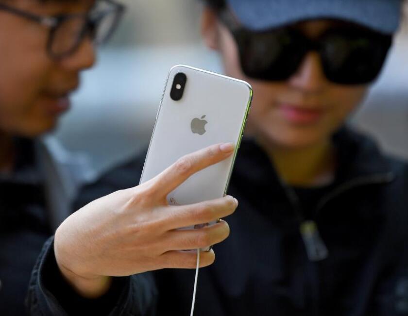 Una joven que observa un iPhone. EFE/Archivo