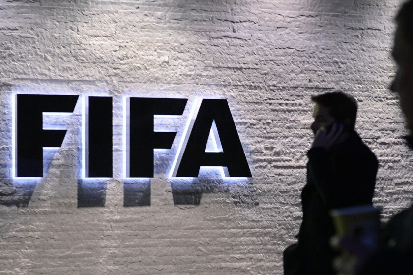 A man stands in front of the logo at the FIFA headquarters in Zurich, Switzerland on Dec. 2. (Walter Bieri/Keystone via AP)