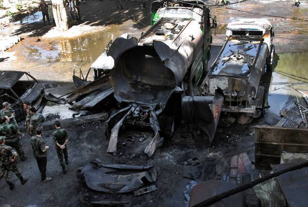 Syrian soldiers take in the scene of a bombing outside a hotel in Damascus, the capital. Three people were injured.