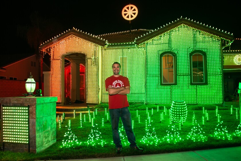 David Peace stands in front of his Escondido home, decked out with 35,000 pixel lights on which he produces a multimedia extravaganza that got him on national television last year.