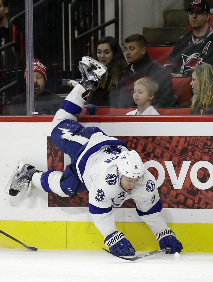 Tampa Bay Lightning's Tyler Johnson (9) is upended during the first period of an NHL hockey game against the Carolina Hurricanes in Raleigh, N.C., Sunday, Nov. 1, 2015. (AP Photo/Gerry Broome)