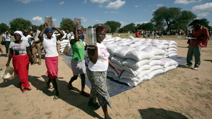 Women carry maize meal during a food distribution in Mwenezi, Zimbabwe, in June 2016. The World Food Program, the U.N. Food and Agriculture Organization and the government of Zimbabwe distributed food in a bid to alleviate the effects of climate-related disasters.
