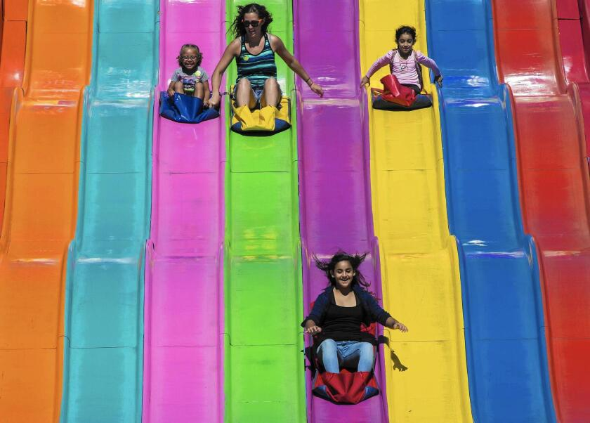"""Orange County Fair visitors going down a giant slide seemed happy to welcome the fair's 2014 theme, """"Summer Starts Here."""""""