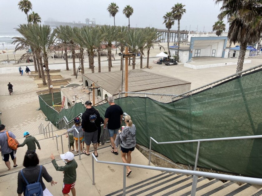 Visitors walk down the new stairway near the Oceanside pier amphitheater on Friday.