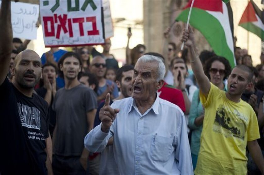 A protester shouts slogans as others hold Palestinian flags during a demonstration against an Israel's plan to relocate nearly 30,000 Bedouins from the southern Negev desert, in Tel Aviv, Israel, Monday, July 15, 2013. Hundreds of protesters have staged demonstrations in Israel against a plan to resettle nomadic Bedouin Arabs in the southern Negev desert. Arab rights groups called the protests. They are fighting a bill that would move thousands of Bedouins into government-recognized villages. Be