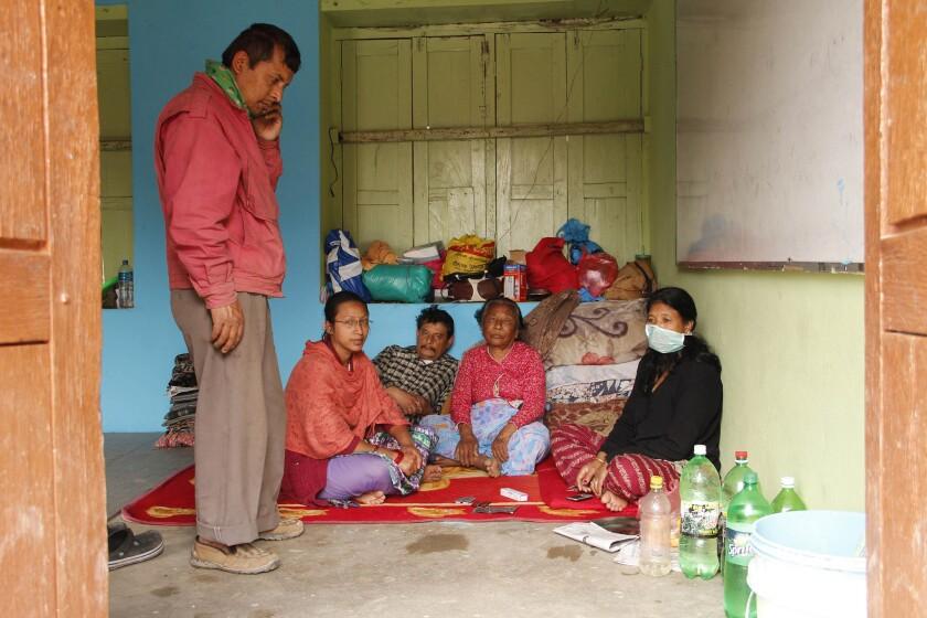 Nem Tamrakar, left, and his family take refuge Friday in a school classroom in Bhaktapur, Nepal.