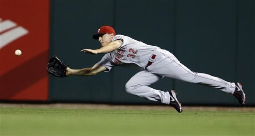 Cincinnati Reds right fielder Jay Bruce dives to catch a ball hit by St. Louis Cardinals' Yadier Molina to end the fifth inning of a baseball game, Tuesday, April 9, 2013, in St. Louis. (AP Photo/Jeff Roberson)