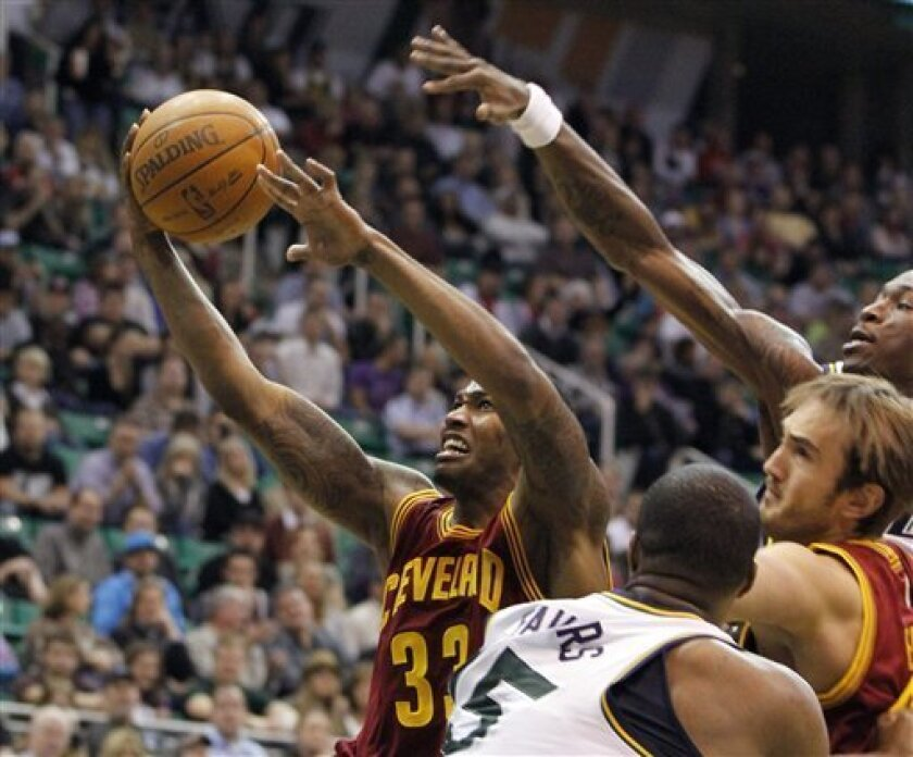 Cleveland Cavaliers forward Alonzo Gee (33) drives past Utah Jazz forwards Derrick Favors (15) and Josh Howard, right, and teammate center Semih Erden, second from right, during the first half of an NBA basketball game, Tuesday, Jan. 10, 2012, in Salt Lake City. (AP Photo/Jim†Urquhart)