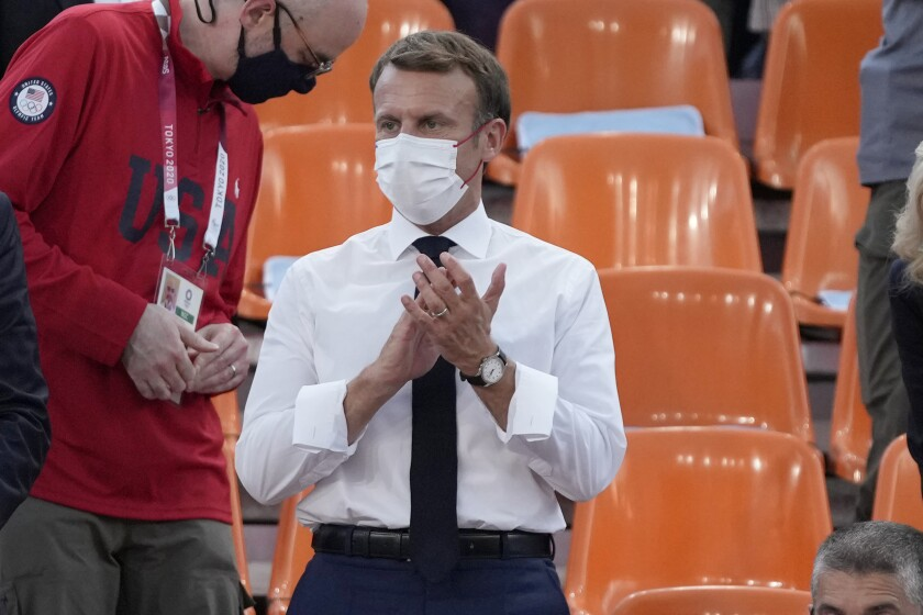 French President Emmanuel Macron applauds as he watches a women's 3-on-3 basketball game between France and the United States at the 2020 Summer Olympics, Saturday, July 24, 2021, in Tokyo, Japan. (AP Photo/Jeff Roberson)