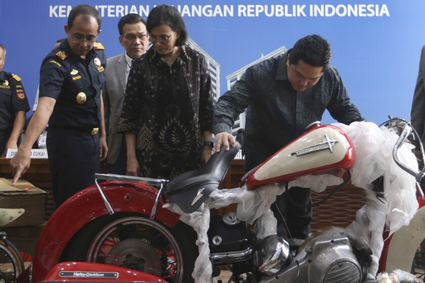 Indonesian Finance Minister Sri Mulyani Indrawati, second from right, and Minister of State-Owned Enterprises Eric Thohir, right, inspect a Harley Davidson motorcycle found by customs officials on a Garuda Indonesia's new Airbus A330-900 being delivered from France, prior to the start of a press conference in Jakarta, Indonesia, Thursday, Dec. 5, 2019. Thohir said he will fire and seek the prosecution of the head of the national airline after he was implicated in the smuggling the motorcycle into the country on the new jet. (AP Photo/Achmad Ibrahim)