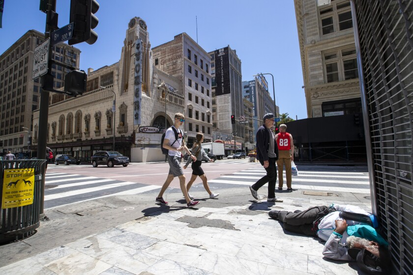 LOS ANGELES, CALIF. -- MONDAY, MAY 20, 2019: Pedestrians walk past a homeless man laying on the side