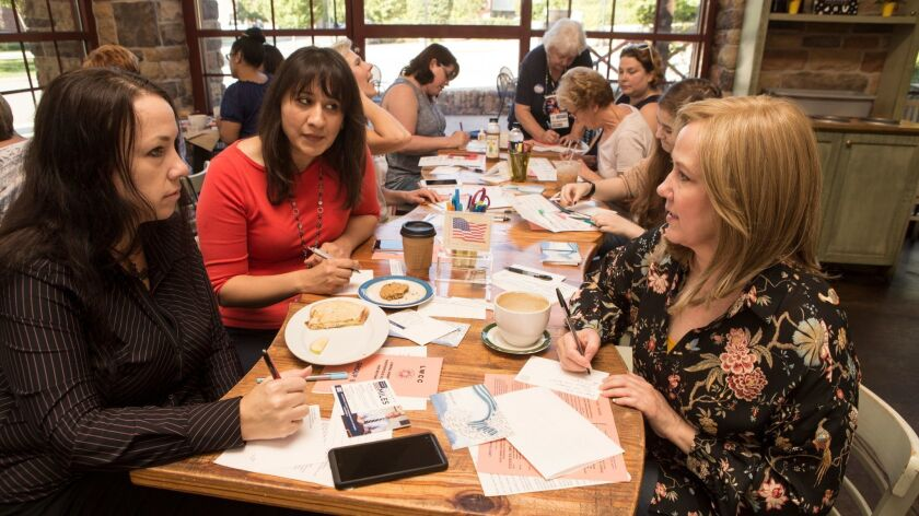 Talking politics, from left, Becky Conner, Sidra Butt and Kim Drew Wright meet with about 20 members of the Liberal Women of Chesterfield County at a local coffee shop in the suburbs of Richmond, Va.
