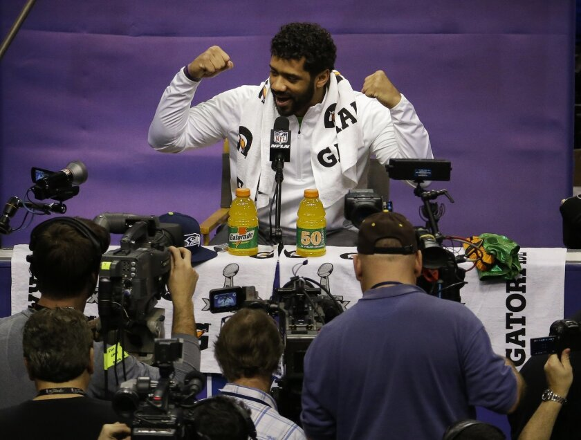 Seattle Seahawks' Russell Wilson gestures during media day for NFL Super Bowl XLIX football game Tuesday, Jan. 27, 2015, in Phoenix. (AP Photo/Charlie Riedel)