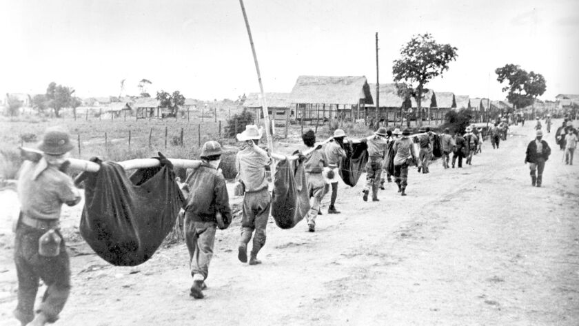 Nearing the end of the Bataan Death March, a thinning line of American and Filipino prisoners of war carry casualties in improvised stretchers as they approach a Japanese POW camp in April 1942.