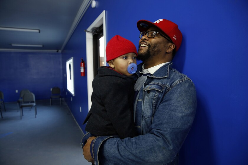 Andrew Jackson II with son Tamir, 1, as he waits to get his hair trimmed in Jeanerette, La. Jackson attended President Obama's first inauguration in 2008 with his mother and father, Brenda and Andrew Jackson.