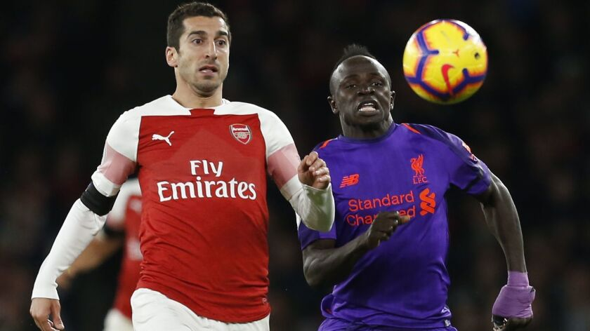 Arsenal midfielder Henrikh Mkhitaryan, left, and Liverpool striker Sadio Mane try to chase down the ball during a Premier League game on Nov. 3.