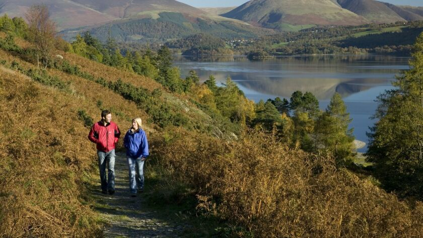 A couple walk along a footpath in England's Lake District.