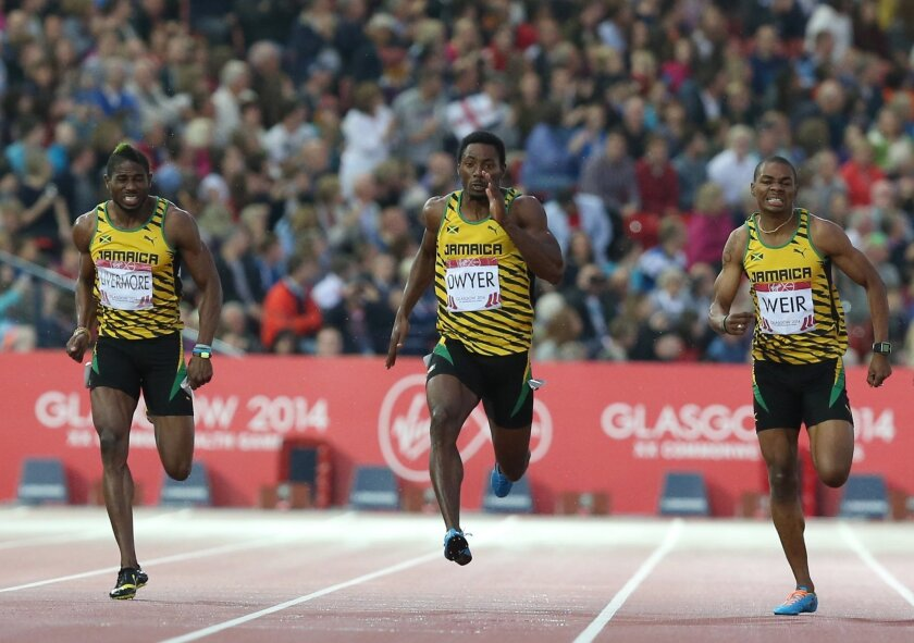 Rasheed Dwyer, centre of Jamaica, leads home a Jamaica 1, 2, 3, with Warren Weir, right, who placed second and Jason Livermore place 3rd in the men's 200 meter race at Hampden Park Stadium during the Commonwealth Games 2014 in Glasgow, Scotland, Thursday July 31, 2014. Dwyer won the gold medal winn