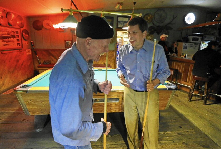 Democratic Sen. Mark Begich, right, jokes with Jimmy Maddox this month at Kito's Kave, a bar in Petersburg, Alaska.