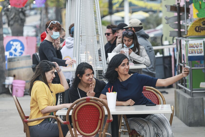 Diners sit outside at the Baja Beach Cafe along the boardwalk in Pacific Beach on Wednesday, May 12, 2021.