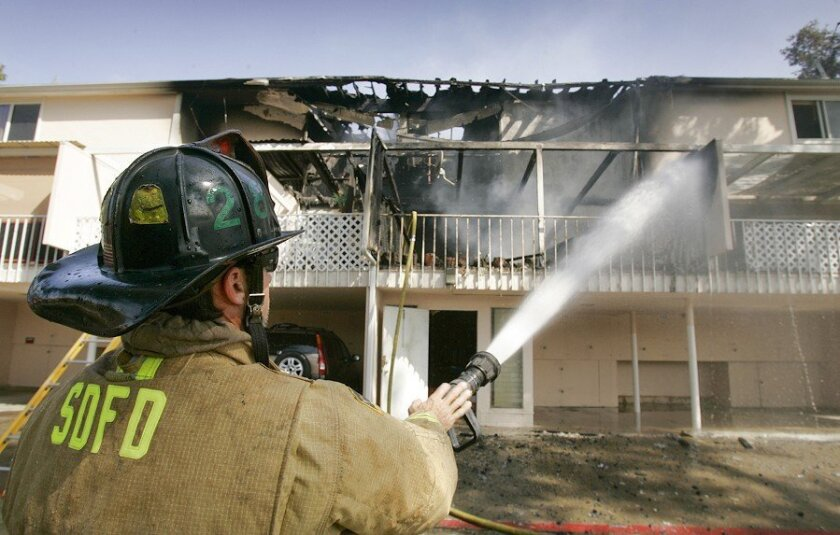 San Diego Fire-Rescue Department Engineer Kevin Abel attends to a condo-complex fire in University City in June 2008.